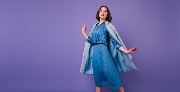 Emocjonalna brunetka kobieta w niebieskim płaszczu, pozowanie na fioletowej ścianie. wewnątrz zdjęcie pięknej krótkowłosej modelki w modnej sukience midi.