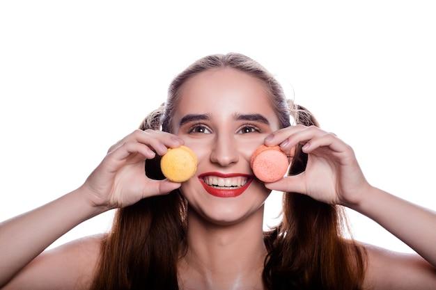 Emocjonalna brunetka młoda kobieta trzyma kolorowe makaroniki
