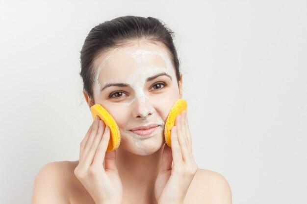 Emocjonalna brunetka nagie ramiona kosmetyki do usuwania makijażu