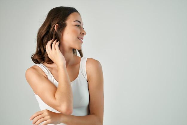 Emocjonalna brunetka versta studio włosów biała koszulka lifestyle