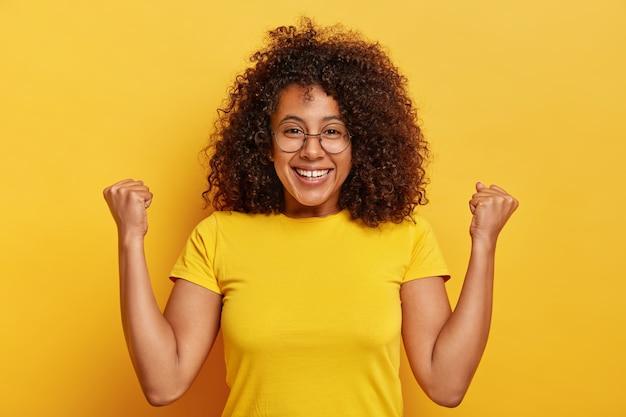 Emocjonalna ciemnoskóra kobieta robi hooray gest, podnosi pięści, uśmiecha się przyjemnie, uśmiecha się rozbawiona, nosi duże okrągłe okulary i swobodną koszulkę, ma świecące kręcone włosy, odizolowane na żółtym tle