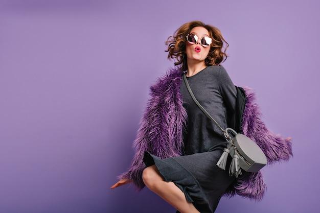 Emocjonalna dama z krótkimi kręconymi włosami, zabawnie tańcząca w okularach przeciwsłonecznych i futrze