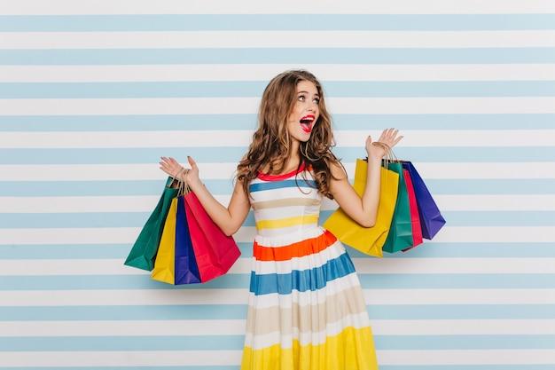 Emocjonalna dziewczyna jest zszokowana dużymi rabatami w czarny piątek i kupuje dużo ubrań. pełnometrażowy portret kobiety w jasnej sukience z torby na zakupy