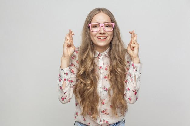 Emocjonalna dziewczyna pokazująca szczęście, znak jej palcami patrząc w kamerę i uśmiechnięty ząb
