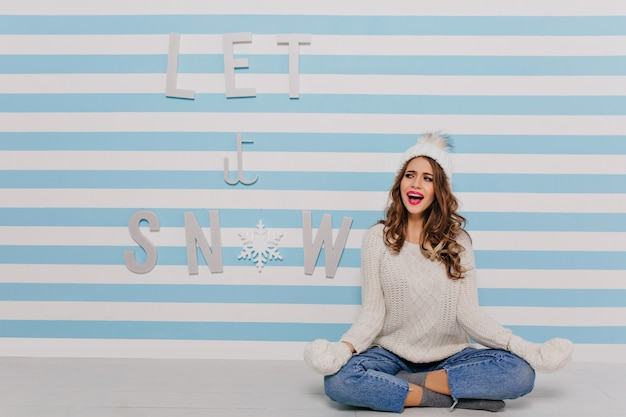 """Emocjonalna dziewczyna siedzi na podłodze w pozie do medytacji. kobieta w ciepłym stylowym stroju nad napisem """"niech pada śnieg"""""""