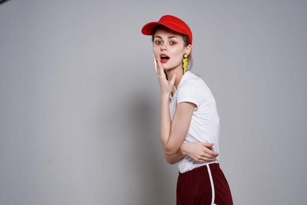 Emocjonalna dziewczyna w czerwonej czapce jasny makijaż żółte kolczyki biżuteria akcesoria