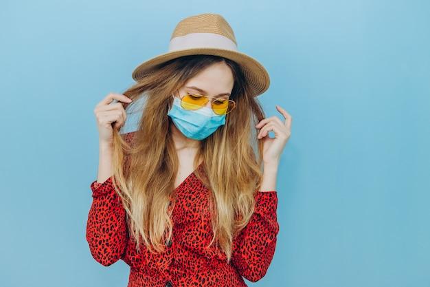 Emocjonalna dziewczyna w czerwonej sukience, kapeluszu i medycznej masce na niebieskim tle. anulowano podróż z powodu epidemii koronawirusa.