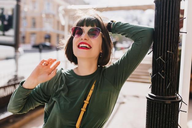 Emocjonalna dziewczyna w okularach przeciwsłonecznych, śmiejąc się na ulicy. zdjęcie wspaniałej kobiety rasy kaukaskiej o czarnych włosach wyrażającej szczęście.