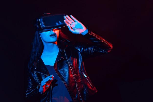 Emocjonalna dziewczyna w okularach wirtualnej rzeczywistości pogrąża się w cyberprzestrzeni