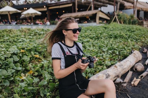 Emocjonalna dziewczyna w stroju vintage siedzi na trawniku z aparatem. śmiejąca się fotografka w czarnych okularach przeciwsłonecznych, zabawy w parku w letni dzień.