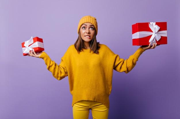 Emocjonalna dziewczyna w żółte spodnie pozuje z prezentami. kryty portret spektakularnej kobiety w dorywczo kapelusz gospodarstwa przedstawia na fioletowo.