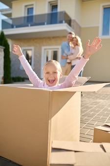 Emocjonalna dziewczyna z uniesionymi rękami siedzi w pudełku