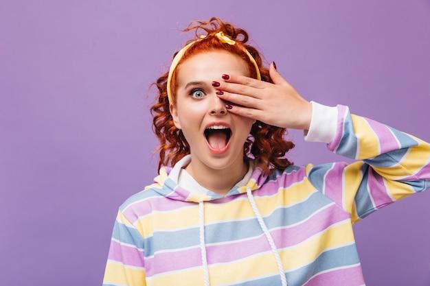 Emocjonalna dziewczyna zakrywa oko dłonią i patrzy z przodu na fioletową ścianę