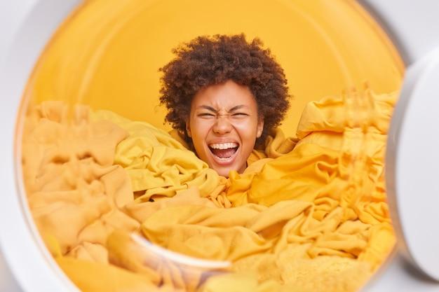 Emocjonalna gospodyni domowa z kręconymi włosami pozuje w pralce zakopanej w praniu