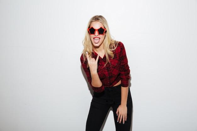 Emocjonalna kobieta jest ubranym okulary przeciwsłonecznych pokazuje rockowego gest.