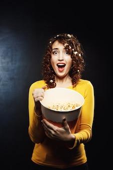 Emocjonalna kobieta ogląda horror i wygląda przerażona, krzycząc głośno