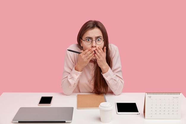 Emocjonalna kobieta perfekcjonistka patrzy ze strachem, trzyma ręce na ustach, nosi optyczne okrągłe okulary, wykorzystuje do pracy nowoczesne technologie