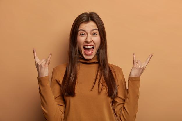 Emocjonalna kobieta pokazuje rogi do góry, wraca z koncertu rock n roll, lubi świetną muzykę, głośno wykrzykuje, nosi brązowy golf, odizolowany na beżowej ścianie studia