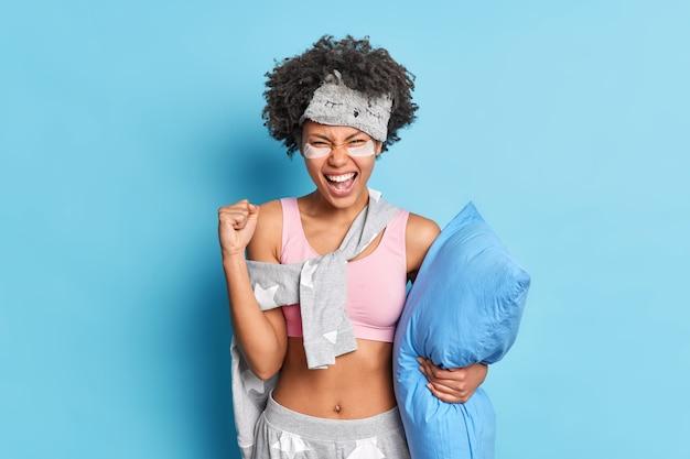 Emocjonalna kobieta przygotowuje się do snu zaciska pięść i krzyczy głośno pozuje z poduszką, nosi maskę do spania i piżamę odizolowaną od niebieskiej ściany, ma podkładki pod oczami