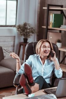 Emocjonalna kobieta. stylowa dojrzała bizneswoman rozmawiająca przez telefon z przyjacielem emocjonalnie