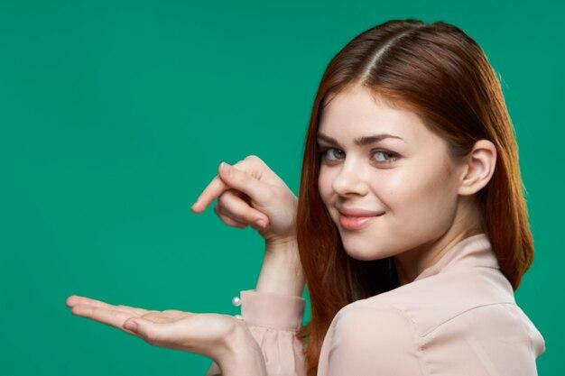 Emocjonalna kobieta trzyma dłoń w pobliżu siebie studio stylu życia na białym tle zielone tło
