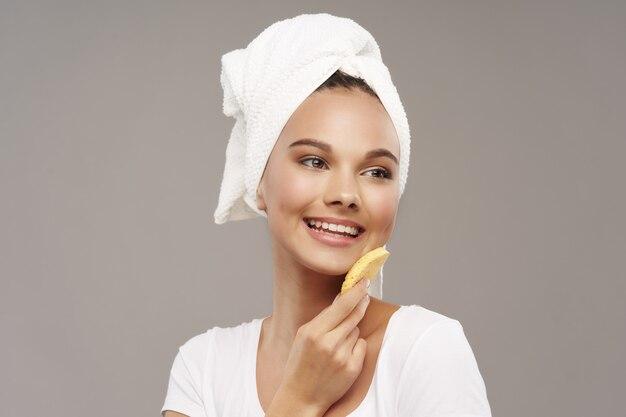Emocjonalna kobieta uśmiecha się i trzyma miękką gąbkę