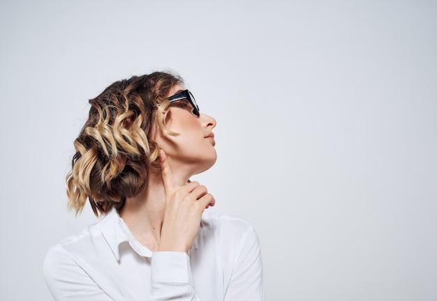 Emocjonalna kobieta w białej koszuli z okularami w dłoniach na jasnym tle kopii przestrzeni
