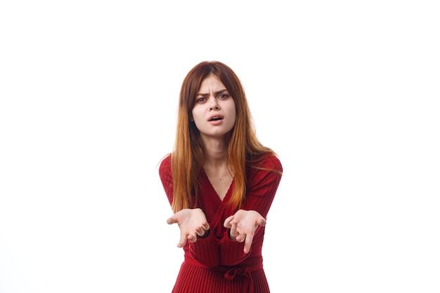 Emocjonalna kobieta w czerwonej sukience gestykuluje rękami jasnym tłem