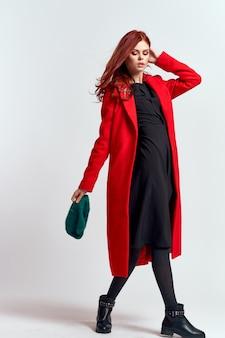 Emocjonalna kobieta w czerwonym płaszczu i kapeluszu w pełni wzrostu na jasnym tle czarne buty stanowią model. wysokiej jakości zdjęcie
