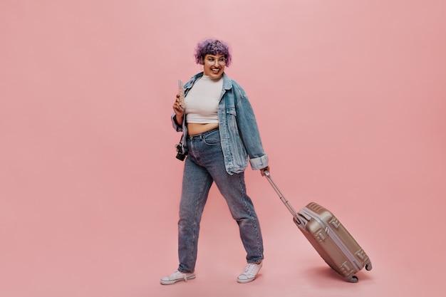 Emocjonalna kobieta w dżinsach i białych trampkach trzyma bilety i szarą walizkę. dama w okularach i lekkim topie śmiejąca się na różowo.