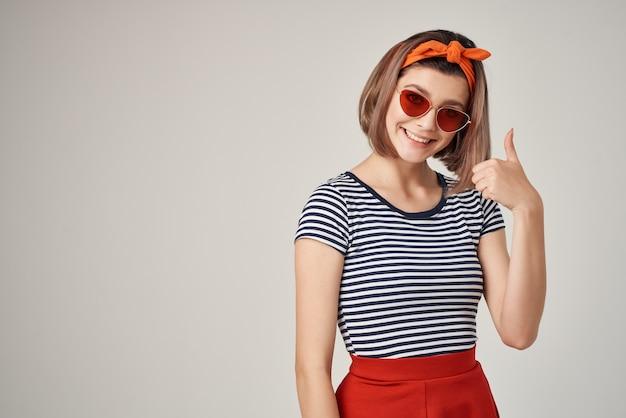 Emocjonalna kobieta w okularach przeciwsłonecznych w paski tshirt w nowoczesnym stylu pozowanie na jasnym tle