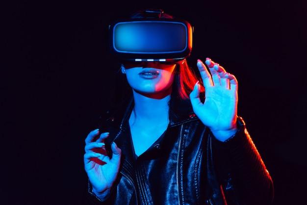 Emocjonalna kobieta w okularach wirtualnej rzeczywistości pogrąża się w cyberprzestrzeni