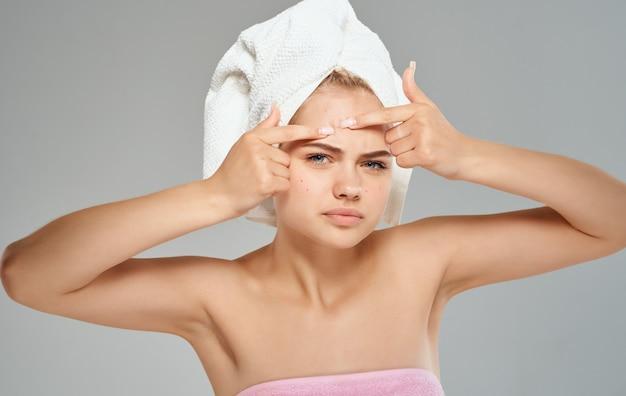 Emocjonalna kobieta wyciska pryszcze na czole i ręcznik na głowie.