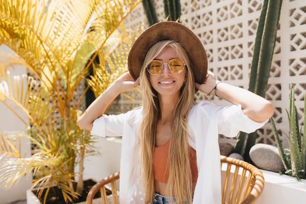 Emocjonalna kobieta z blond prostymi włosami z zamkniętymi oczami w restauracji ośrodka. urocza kaukaski modelka w brązowym kapeluszu uśmiechnięta podczas sesji zdjęciowej w kawiarni.