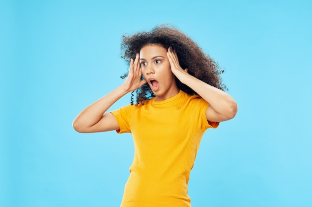 Emocjonalna kobieta z kręconymi włosami w żółtym tshirt niebieskim tle