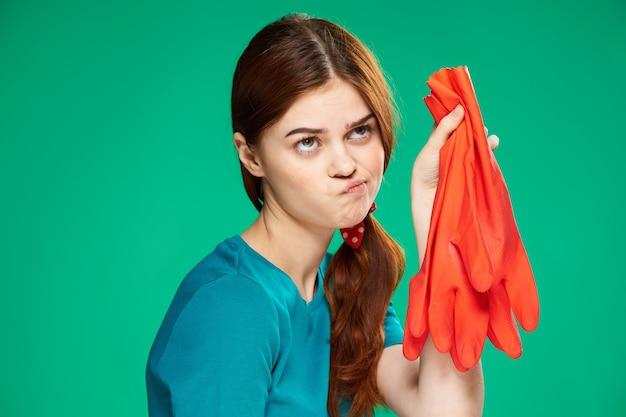 Emocjonalna kobieta z niezadowolonym wyrazem twarzy, trzymając gumowe i czerwone rękawiczki do czyszczenia