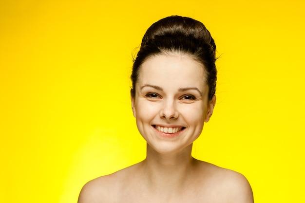 Emocjonalna kobieta z odkrytymi ramionami w modnych okularach zebrała żółte włosy.