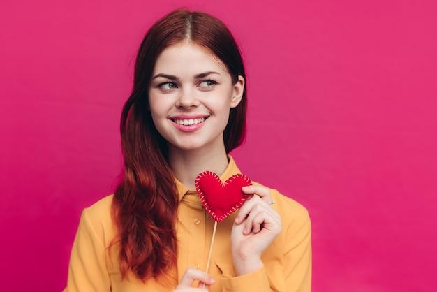 Emocjonalna kobieta z sercem na kiju i żółtej koszuli na różowym tle. wysokiej jakości zdjęcie