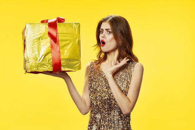 Emocjonalna kobieta z sukienką trzymająca prezent