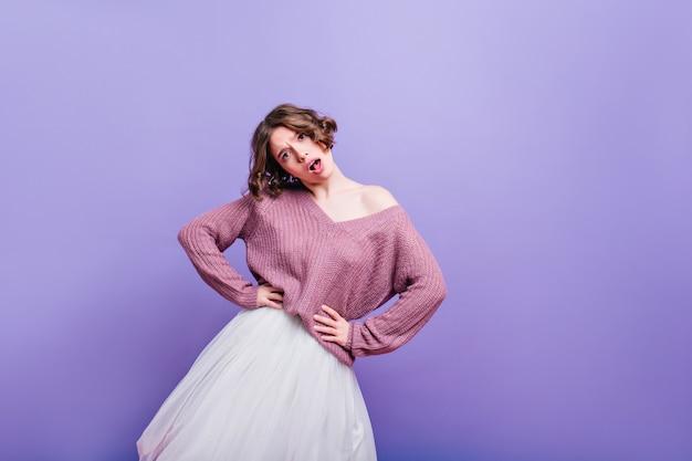 Emocjonalna kochana dziewczyna z ciemnymi kręconymi włosami pozuje w długiej modnej spódnicy. śliczna kaukaska kobieta nosi miękką fioletową koszulę do tańca