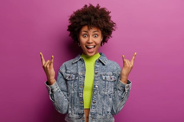 Emocjonalna kręcona kobieta odwiedza festiwal muzyczny, reaguje na ulubioną piosenkę