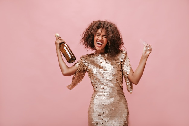 Emocjonalna młoda dama z brunetką falowanymi włosami w beżowym błyszczącym stroju, śmiejąca się z zamkniętymi oczami i trzymająca butelkę z napojem i szklanką na różowej ścianie..