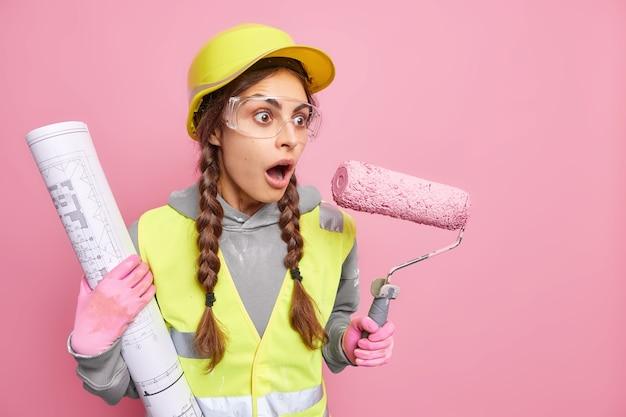 Emocjonalna młoda kobieta architekt patrzy zszokowana, dysząc z wielkiego cudu, ma pewne problemy z budową, trzyma plan budowy i wałek do malowania odizolowane na różowej ścianie wolne miejsce