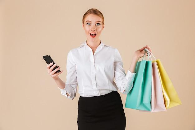 Emocjonalna młoda kobieta biznesu trzymając torby na zakupy za pomocą telefonu komórkowego.