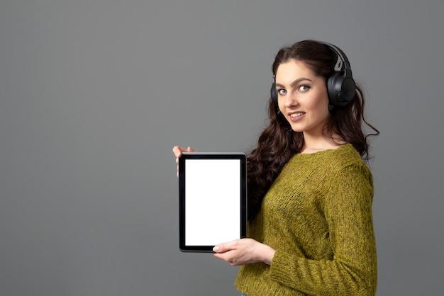 Emocjonalna młoda kobieta pokazująca komputer typu tablet z pustym ekranem dotykowym z miejsca na kopię, na białym tle na szarym tle