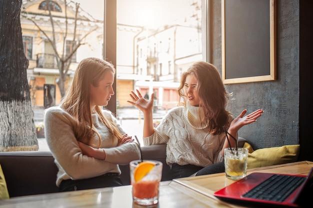 Emocjonalna młoda kobieta siedzi razem ze swoją przyjaciółką. są w środku przy stole. modeluj fale rękami. kolejny jej wysłuchaj. na stole są laptopa i szklanki z napojami.
