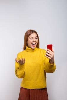 Emocjonalna młoda kobieta używa smartphone