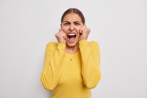 Emocjonalna młoda kobieta wykrzykuje głośno trzymając usta szeroko otwarte, krzyczy nosi swobodny żółty sweterek ma nieszczęśliwy, stresujący wyraz na białym tle nad szarą ścianą
