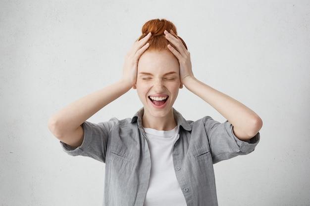 Emocjonalna młoda kobieta z rudymi włosami i piegami, mocno zamykająca oczy i krzycząca z podniecenia i pełnego niedowierzania, trzymając ręce na głowie. pozytywne ludzkie emocje, uczucia, postrzeganie życia
