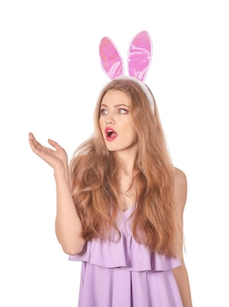 Emocjonalna młoda kobieta z uszami królika wielkanocnego na białym tle